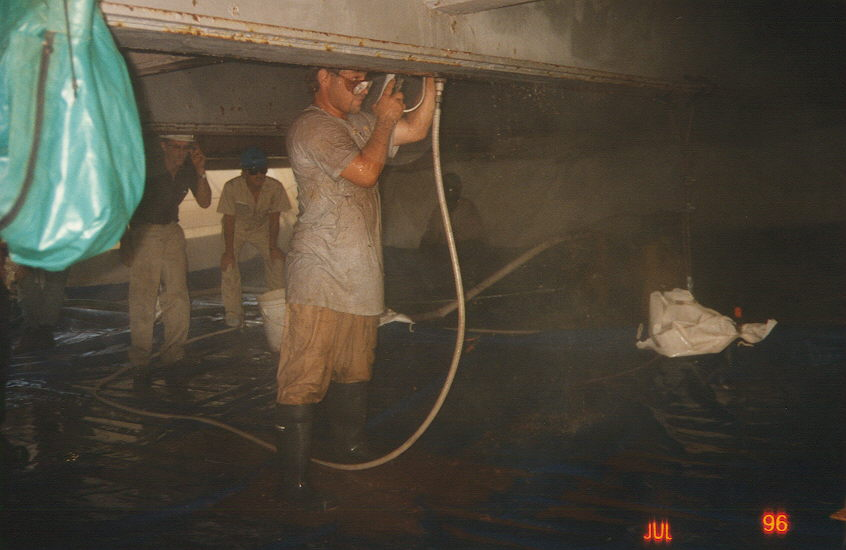 Skilled workers using water jets to remove paint under bridge.jpg