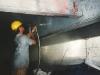 Worker water jet cleaning under bridge.jpg
